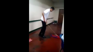 A student mopping the floor using a flag.