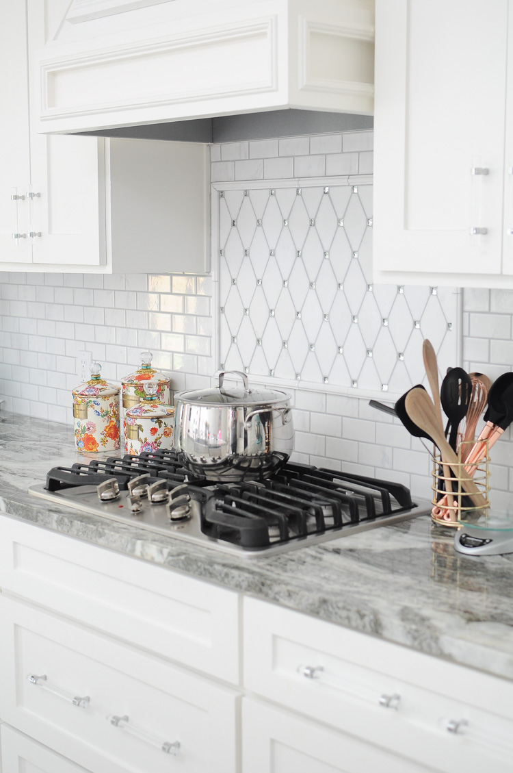 A bright white kitchen with a jeweled backsplash and flower market canisters by MacKenzie-Childs.