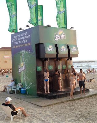Mujeres en bikini en duchas o regaderas de Sprite en la playa.