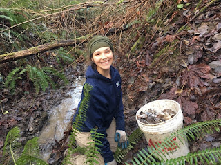 Stevie Knapp smiles as she picks up bottles along a section of Longfellow Creek during her MLK Day debris cleanup project.