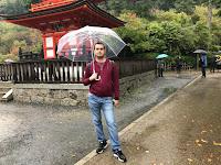 Carlos con el paraguas sintiendo el agua pura de Kiyomizu