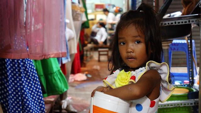 Enfant khmère dans les allées du marché Olympic à Phnom Penh. Photographie par Christophe Gargiulo.