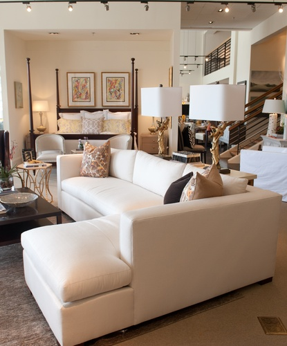 White L-shaped couch with accent pillows with an accent table holding two lamps with gold sculpted bases and white shades, in the background a large bed with a dark wood canopy frame has a COCOCOZY pillow on it