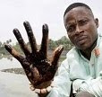 Eric Dooh holds up a hand covered in oil from a creek near his former home, the now abandoned village of Goi.