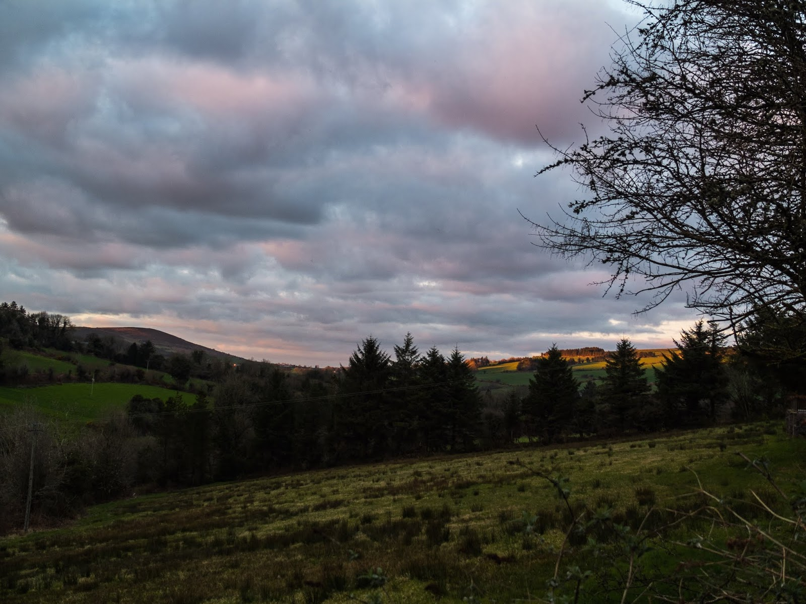 Pink clouds over fields and mountains at sunset in Co.Cork, Ireland.