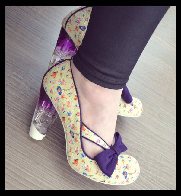 close up of feet wearing Irregular Choice cream floral shoes with purple bow and perspex heel