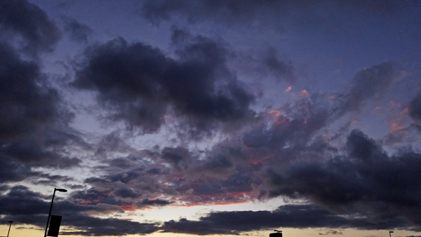image of a stormy sky at sunset, with dark purple clouds haloed in bright pink