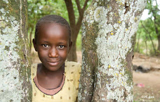 A girl leans against a tree in the village of Usoma — CDC photo