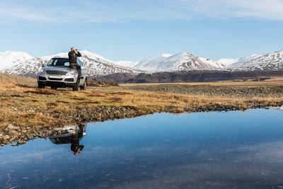 Hombre divisando el paisaje sobre el capó de su coche por carreteras recién abiertas en abril