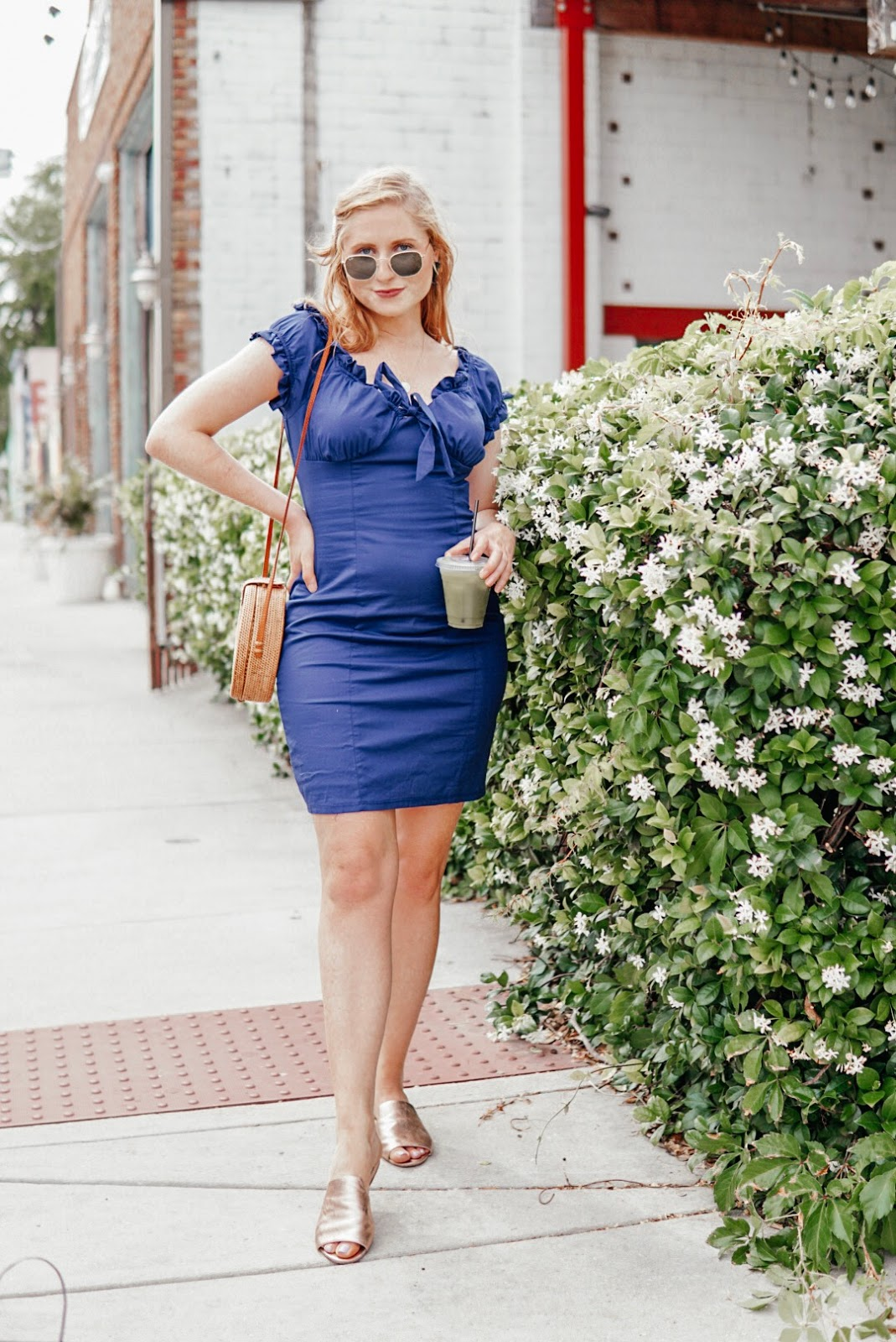 tampa blogger amanda burrows is wearing a navy ruffle dress from francesca's holding a matcha tea from Intermezzo Coffee. She is standing outside Green Bench Brewing. She is wearing Ray Ban Sunglasses and carrying a round rattan circle bag. She is smiling at the camera and standing next to jasmine flowers in St. Petersburg, Florida.