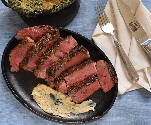 Grilled ribeye steak with compound butter of roasted garlic, green peppercorns, smoked red chile