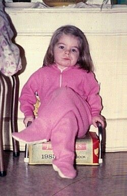 image of me as a toddler, sitting in my grandmother's kitchen in pink footie pajamas with my legs crossed, scowling