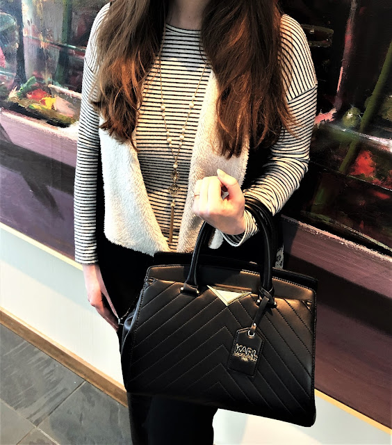 Model is wearing black and white outfit consisting of a striped sweater, vest, pants, boots, a tote bag, and gold jewelry.