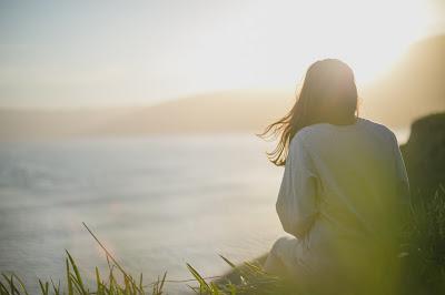 Femme de dos, admirant le paysage de mer, lever de soleil et verdure devant elle