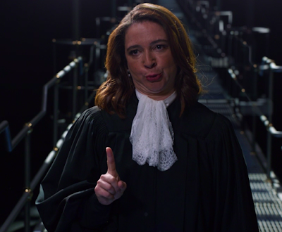 The Judge (Maya Rudolph), wearing a black judge's robes and a fluffy white collar thing, making a weird face where she's pulled her chin back so there are rolls in her neck, and she's holding up one finger of her right hand