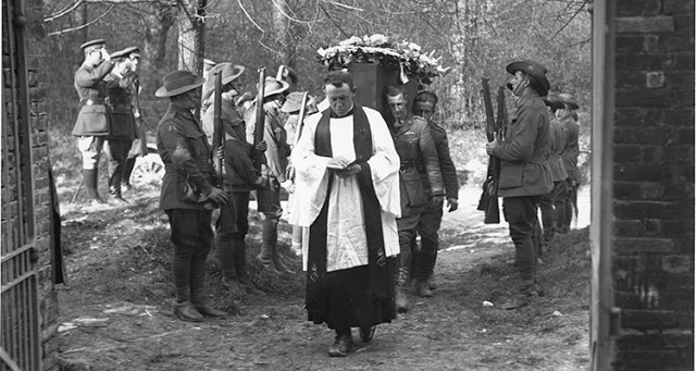 Photo of the funeral of Manfred von Richthofen, The Red Baron, April 22, 1918, No.3 Squadron lays to rest an old adversary, at Bertangles Cemetery, France. A priest walks through church gates followed by Allied soldiers carry coffin as other soldiers salute. Dogfights and other stories of pilots. marchmatron.com
