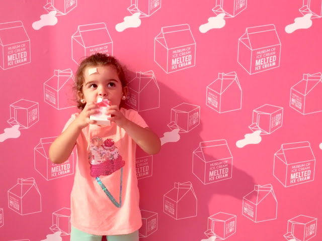 A toddler girl drinking from a pink milk carton in front of a wall with a pink milk cartons print