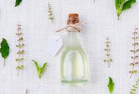 Vidro com óleo e tampa de rolha rodeado de pequenos brotos de plantas sobre tecido rústico branco