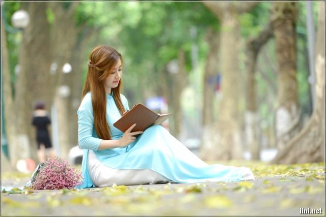 cô gái mặc áo dài ngồi đọc sách