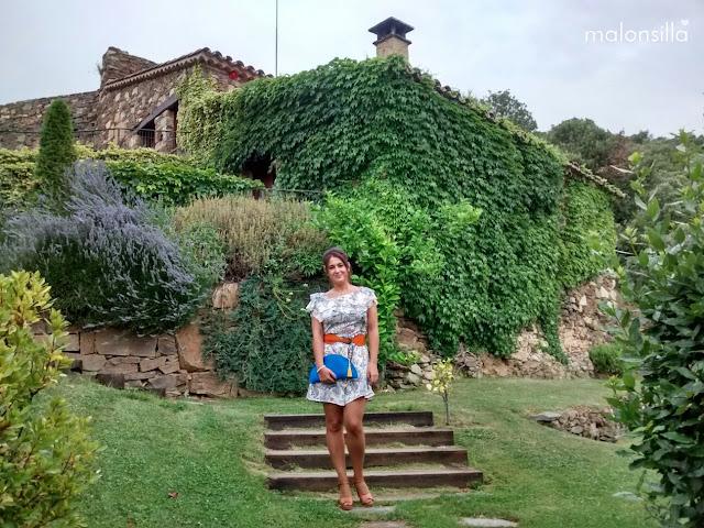 Invitada boda en un jardín con una casa detrás, llevando un vestido corto y un bolso abanico