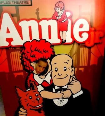 Annie JR poster with girl peering through Annie's face