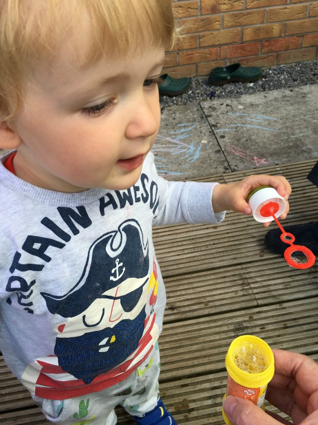 toddler-with-bubble-wand-hand-holding-pot
