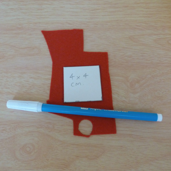 Square cardboard template with red craft felt and a water soluble fabric marker
