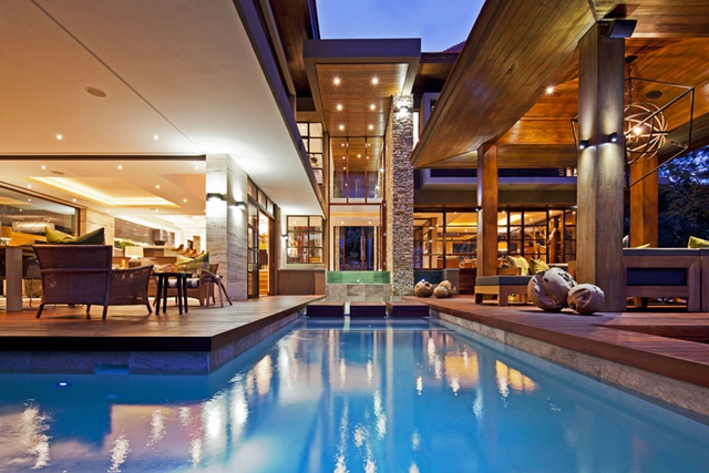 View of the house with pool and small waterfall in the Contemporary South African SGNW House by Metropole Architects