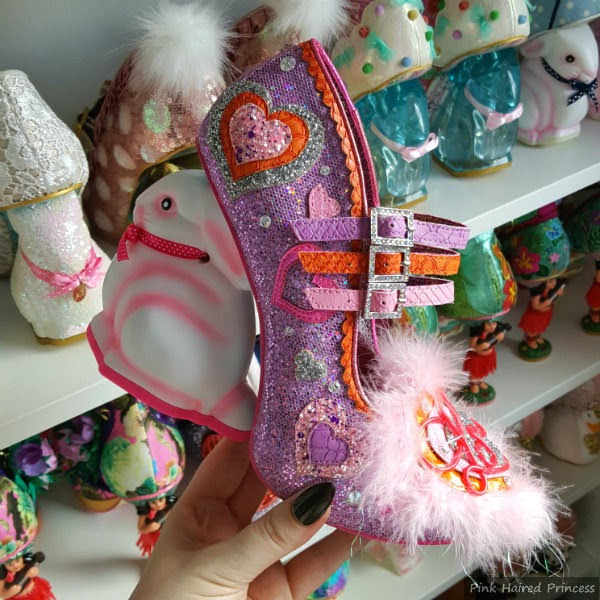 purple embellished shoe in hand with fluffy toe and neon detail, shoe shelves in background