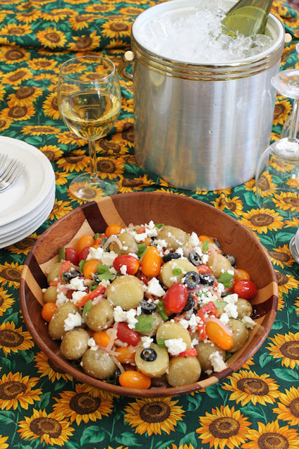 Food Lust People Love: Pumped up potato salad combines new potatoes with charred red peppers, tomatoes, olives, feta and basil for a wonderful summer salad.