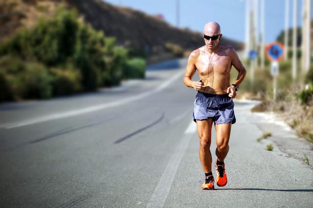 Man wearing head phones running on the road