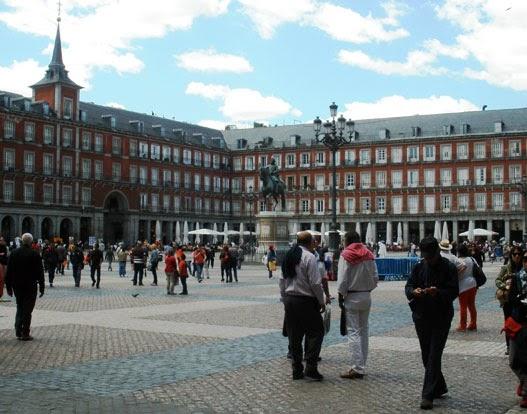 Plaza Mayor con numerosos paseantes. Se aprecia su estilo barroco con influencia del estilo herreriano. Sobre los adoquines, farolas y la estatua ecuestre de Felipe III.