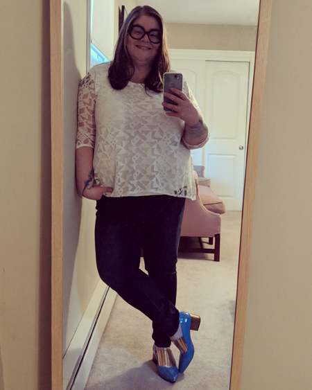 image of me standing in a full-length mirror, with my hair down, wearing black-framed glasses, a white top, dark blue jeans, and blue and gold heeled shoes