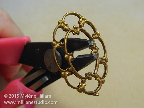 Trimming off all the scroll tips from the inside of the filigree with button shank removers