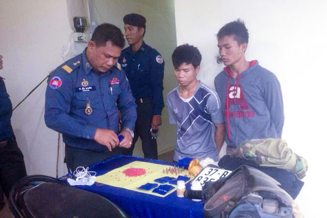Two men arrested for drug trafficking stand at a Stung Treng provincial police station in May as authorities lay out seized methamphetamine pills. Military Police