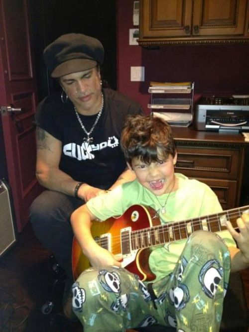 Slash wearing a FUCK YOU Guitar T-shirt while teaching to play guitar to his son
