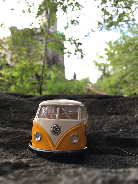 The yellow van on little roundup with a tower and some trees