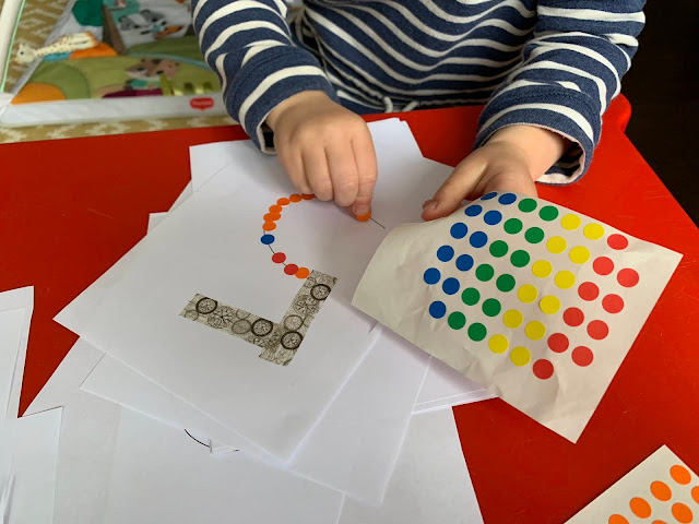 A toddler sticking sticky dots onto the number 5