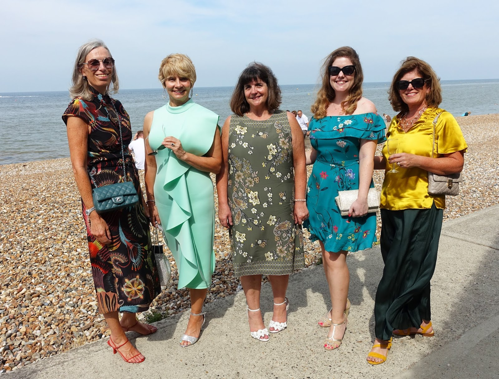 A group of female wedding guests at a Whitstable beach wedding in the August sunshine