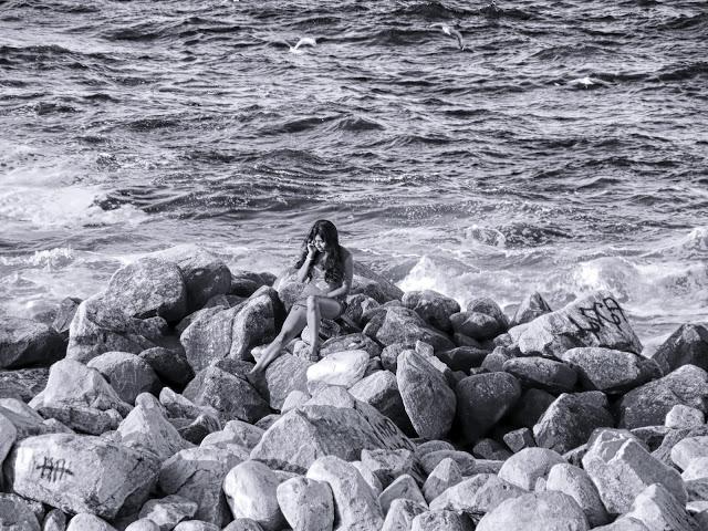 Una joven,un teléfono y rocas en el mar.
