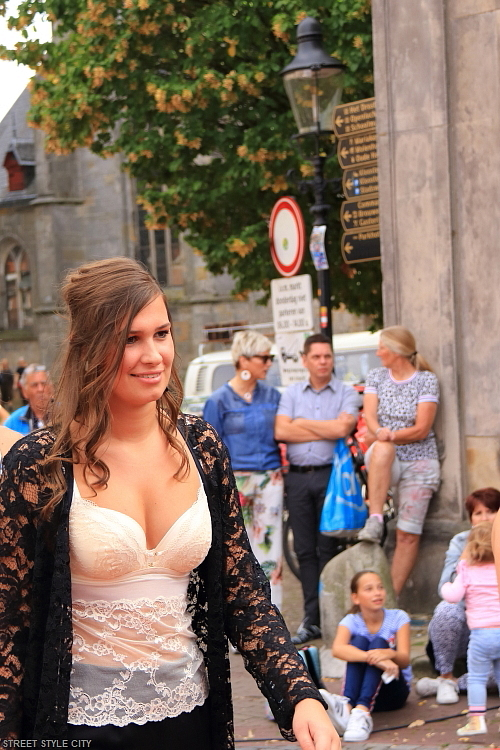 Beautiful dutch girl wearing black and white lace lingerie in the street. Streetstyle fashion look candid