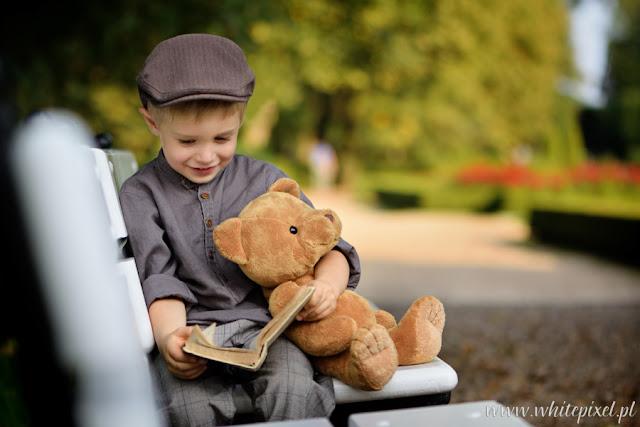 Mały uśmiechnięty chłopiec na sesji na ławce w parku w Kozłówce  czyta książkę misiowi