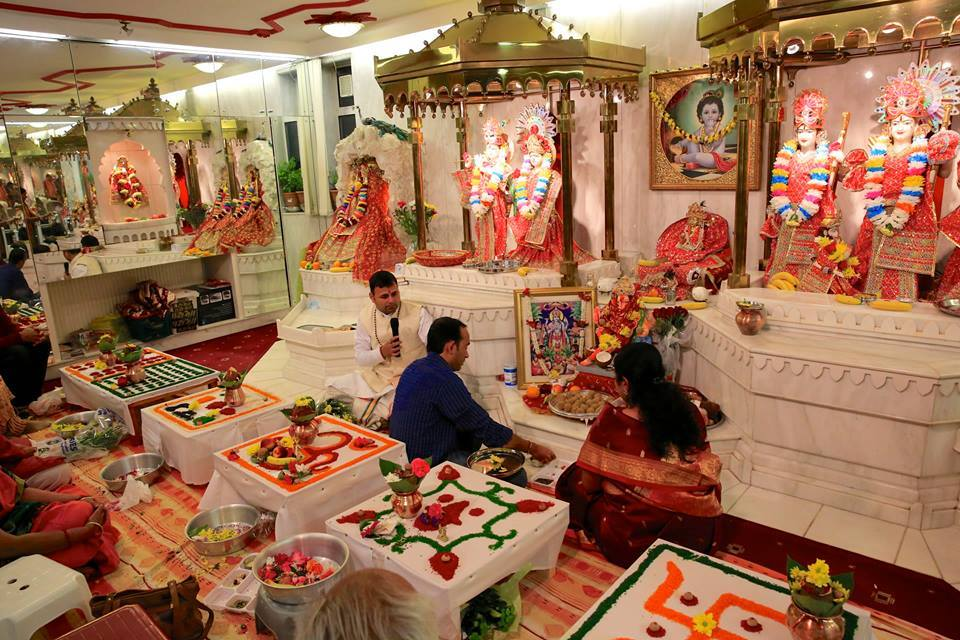 A Vaishnava shrine: Mother and daughter sing devotional hymns as father offers fruits, flowers and light to Radha and Krishna, before whom are enshrined Lord Hanuman and five Shaligrama stones. Traditional sweets have been prepared; incense and small ritual fire have been lit.