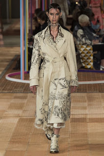 A woman wearing a silver metallic long trench coat with a embroider red rred ose on each shoulder with a silver floral pattern above the hem on a rectangular catwalk on a bright background