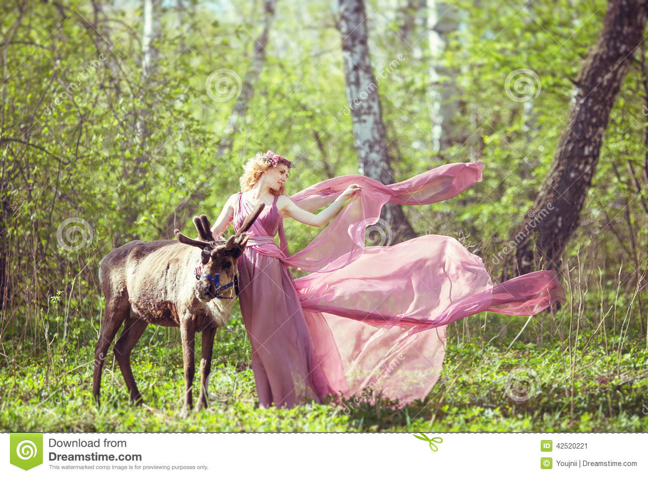 Girl in fairy dress with a flowing train on the dress and reindeer in the forest