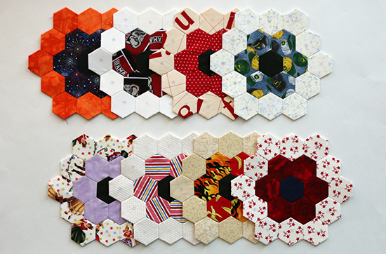 Eight multi-colored EPP hexagon flower blocks with a dark middle ring and light outer ring arranged in two horizontal rows