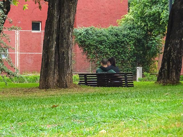 Una pareja enamorada sentados en un banco del parque