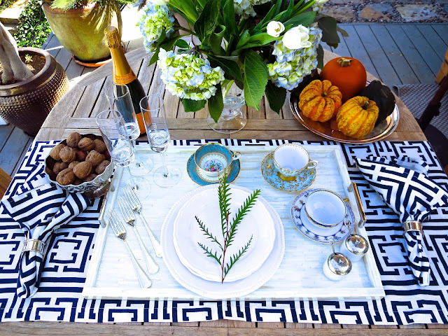 Modern outdoor tea setting with vintage tea cups, a bone and nickle tray, silver flat ware and COCOCOZY napkins and table runner