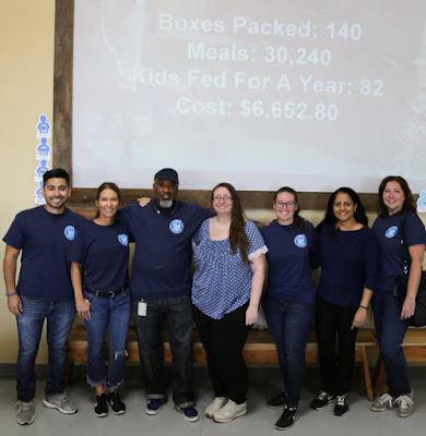 "group shot of team standing in front of a screen that reads, ""Boxes packed: 140, Meals: 30,240, Kids Fed for a Year: 82.  Cost: $6,652.80"