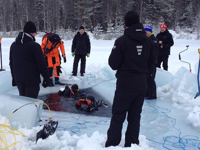 Ihmisiä jäällä avannon ympärillä, pari sukeltajaa lähdössä sukeltamaan